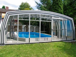 Pool enclosure with open frontal side next to a house